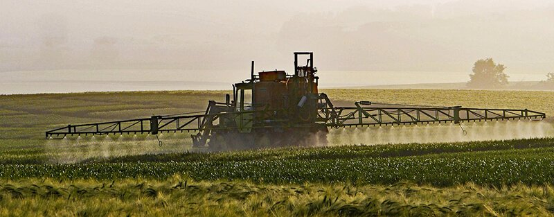 spraying pesticides on field